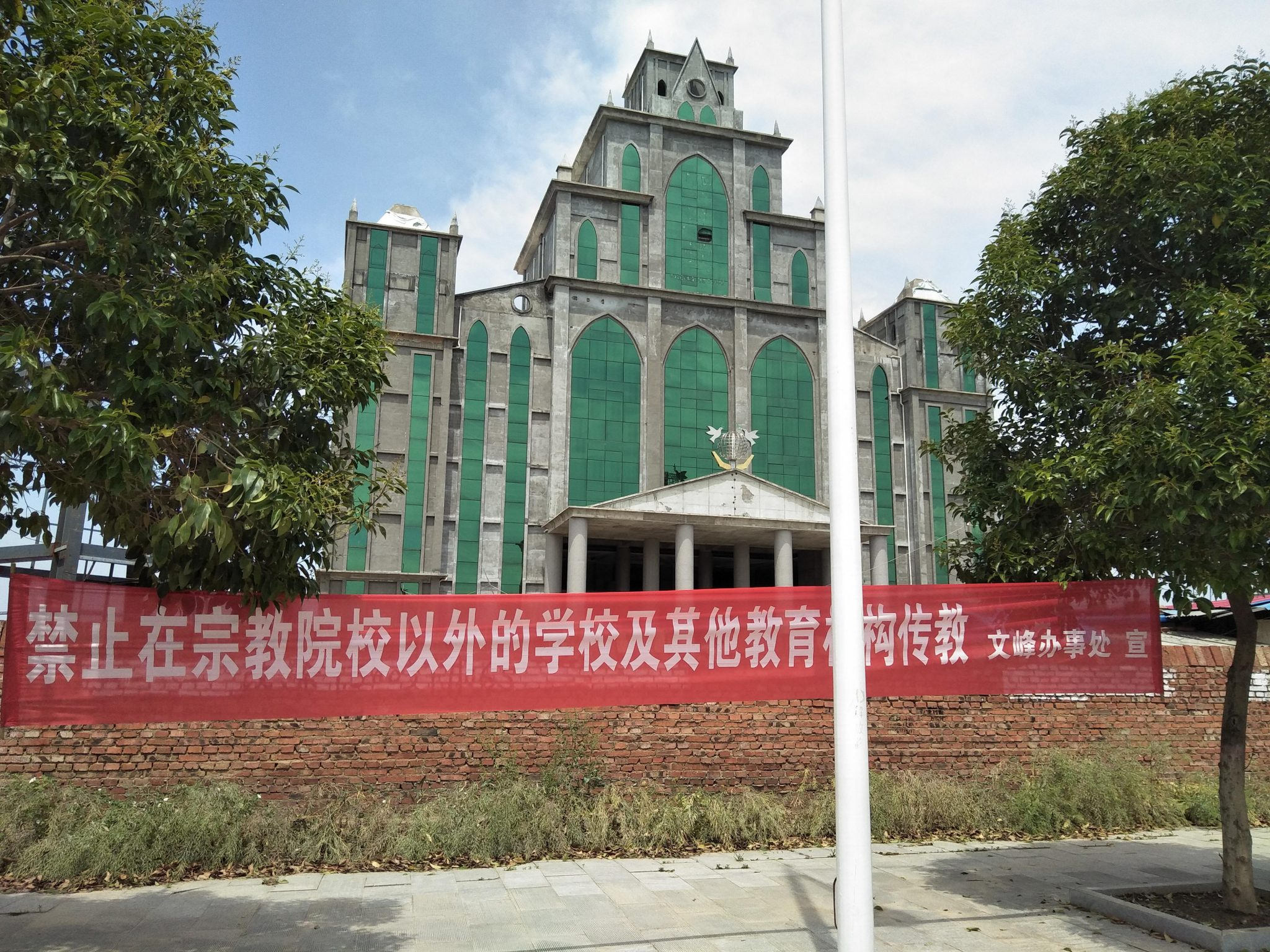 a banner outside the Holy Grace Church in Tanghe County