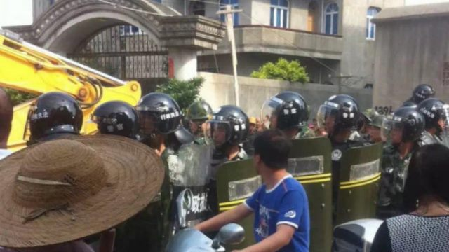 Fully-armed police officers block Christians protesting the demolition.