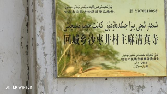 "This Jummah mosque is in Shazaojing village of the Huicheng township in Kumul. The crescent moon and star symbols on top of the mosque have all been removed, and tight wire netting has been attached to the surrounding walls. The notice at the entrance reads: ""Party members, state officials, and minors not allowed in religious establishments."""