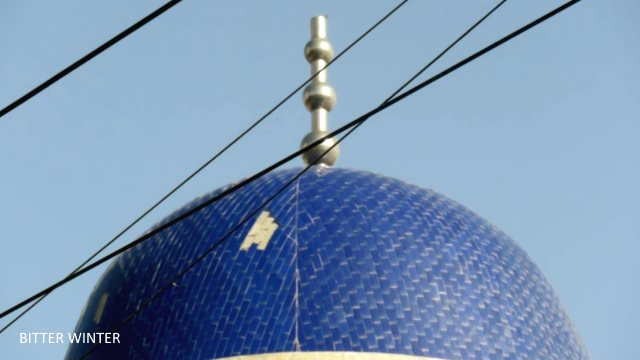 The crescent moon and star symbol atop the mosque across from Huiwangfu in the Yizhou Area of Kumul city has disappeared without a trace.