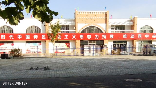 CCP propaganda slogans displayed on the fence of the camp for Uyghur women.