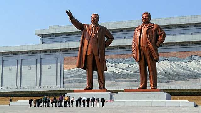 Visitors bowing in a show of respect for North Korean leaders Kim Il-sung and Kim Jong-il on Mansudae (Mansu Hill) in Pyongyang, North Korea.