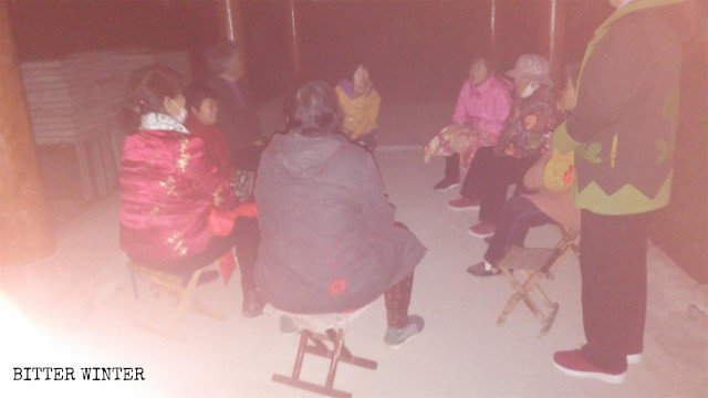 Elderly Christians are gathering in a gazebo outside the village while it is dark outside.