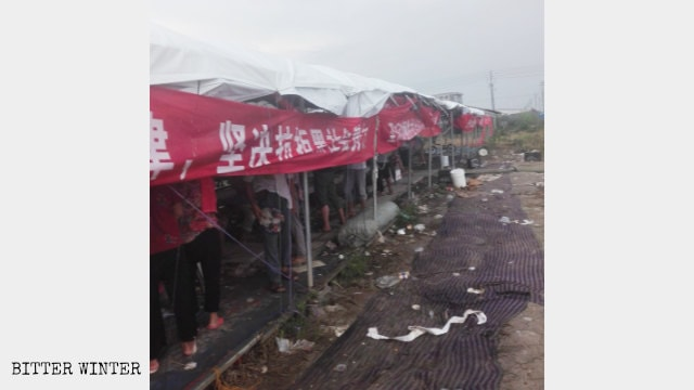 Villagers in their tents guard the farmland