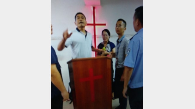 The police ordered Pastor Wang (the woman in the middle) to stop holding gatherings.