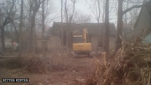 An excavator is forcibly demolishing housing