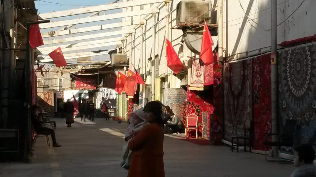 Red flags on display in a market in the city of Turpan. Summer 2018.