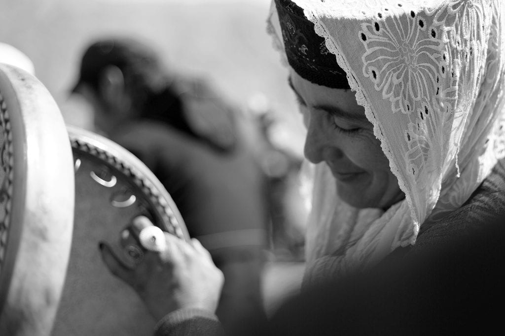 A woman plays the daf (traditional Persian frame drum) at a wedding