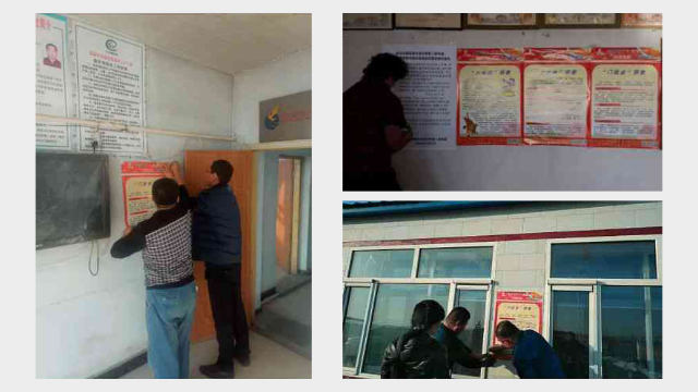 Government employees pasting anti-religion posters on the wall of the village committee office.