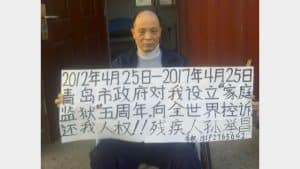 "On April 25, 2017, Sun Juchang holds up a sign at his home, appealing to the world to ""return my human rights to me."" (supplied by Xin Lin from RFA)"