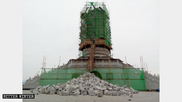 Three-faced Guanyin statue being demolished, and fragments of the structure litter the ground.