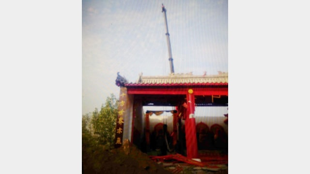 When the hall is being demolished, a crane is lifting the Buddhist statue
