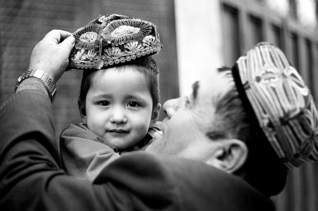 A man put an embroidered doppa (the traditional cap) on his son.