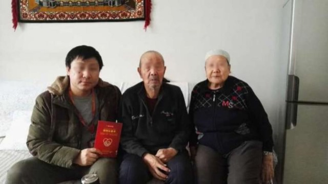 """A Han official's photo with his Uyghur homestay family taken after the signing of """"the homestay card"""""""