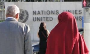 A man and a woman outside the building of the United Nations in Geneva