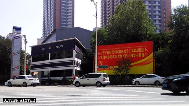 Police station, surveillance cameras, and large propaganda poster in Urumqi.