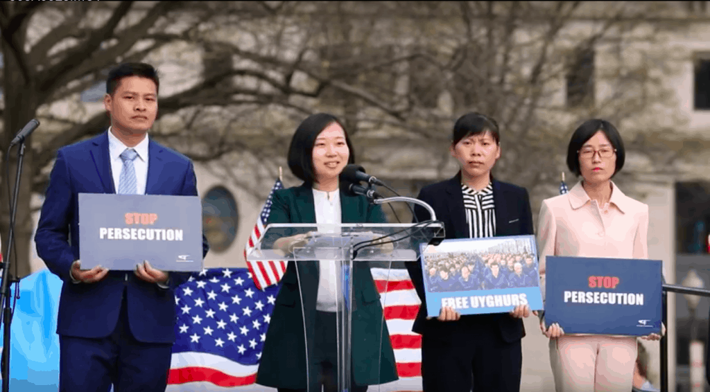 Sister Jiao of The Church of Almighty God speaks, while other members of her Church hold signs of solidarity with the Uyghurs
