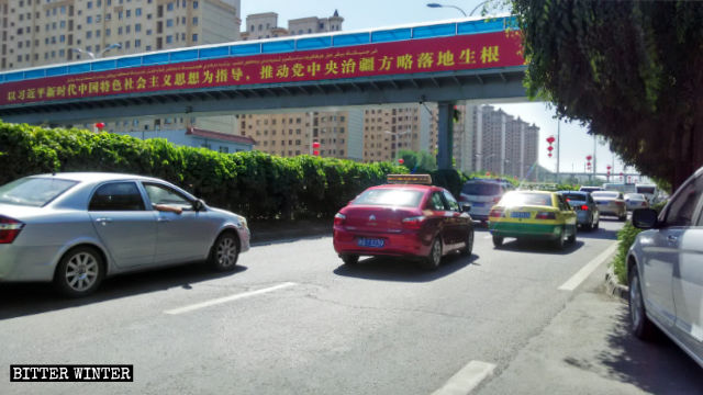 """A propaganda slogan poster in Xinjiang's Urumqi: """"Promote the full implementation of the Party Central Committee's strategy for governing Xinjiang,"""" guided by Xi Jinping's thought."""