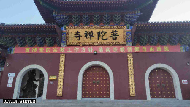 """An utterly ironic CCP propaganda slogan, reading """"Implement the policy of freedom of religious belief,"""" hangs in front of Putuo Temple."""