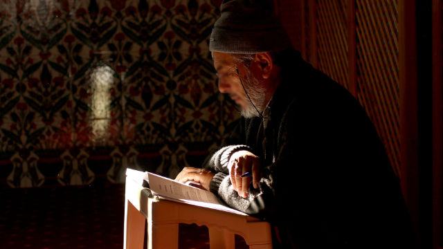Elderly Muslim reading the Quran