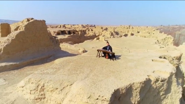 A Han Chinese musician playing the gu zheng on a plateau in the ancient city of Jiaohe, Turpan, during Uyghur festivities to celebrate the beginning of Spring.