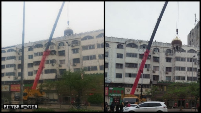 A crane dismantles a round Islamic structure at the top of a building