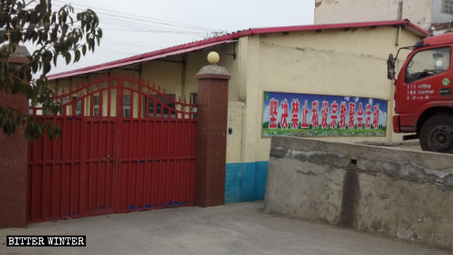 """A banner reading """"Private religious gatherings and activities firmly prohibited"""" is posted on the outer wall of the Three-Self meeting venue in Lugou village."""