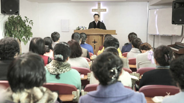 A Korean pastor is giving a sermon