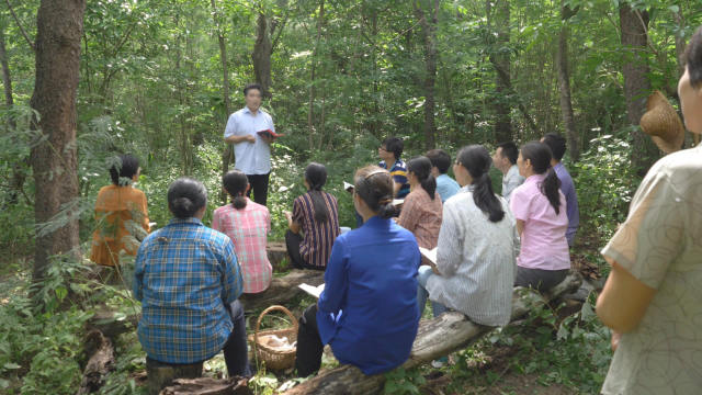 Believers of a house church are holding a meeting in the woods.