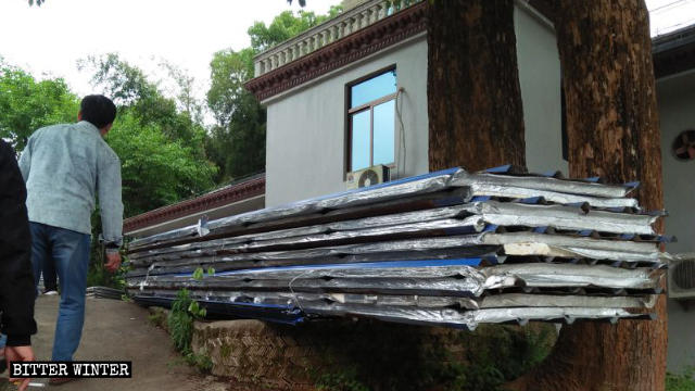 Galvanized iron sheets are placed to the side after being demolished