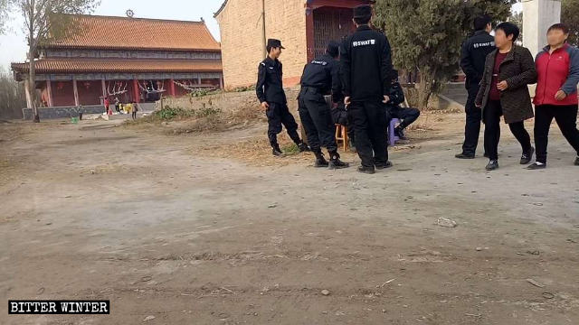 Police stand guard in front of Gulingshan Temple.