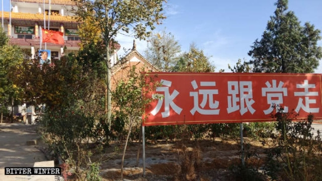 "A sign reading ""Follow the Party forever"" stands in front of Tianyi Temple"