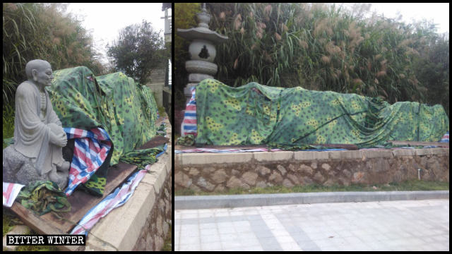The dismantled Arhat statues are stacked in a pile to the side of the road and covered with cloth