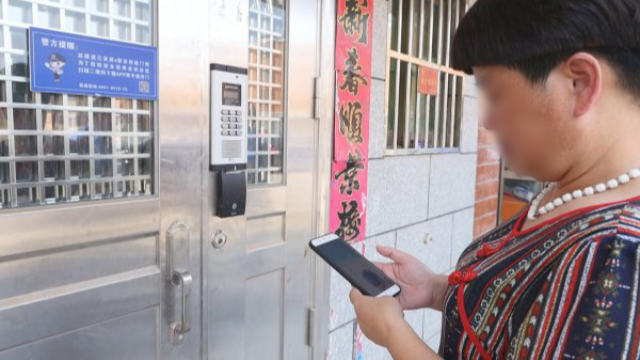 A tenant is using the mobile app to open the smart door lock.