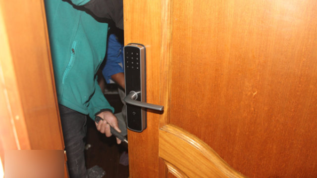 A worker is installing the smart lock at a rental property.