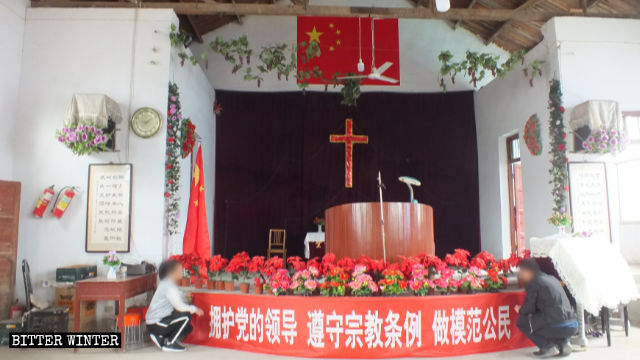 China's national flag is hung on top of the cross inside Xinzhuang Church.
