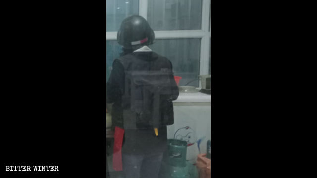 A cafe waitress wears a bulletproof vest and a helmet while at work.