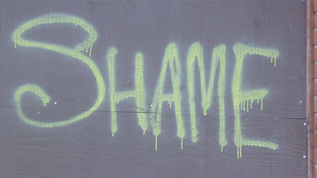 "the word ""shame"" on a wall"