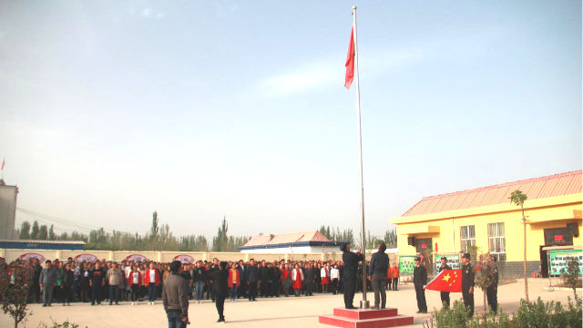The people in a locality in Xinjiang are organized to hold a flag-raising ceremony